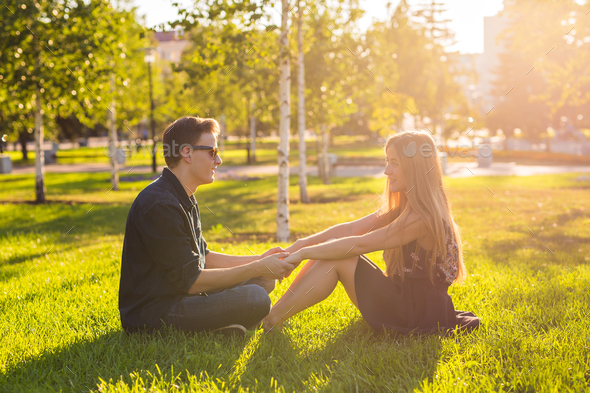 friendship, leisure, summer and people concept - young love couple sitting on grass in park - Stock Photo - Images