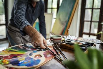 Artist painting artwork at workspace