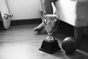 Closeup of trophy on the bedroom floor with basketball grayscale