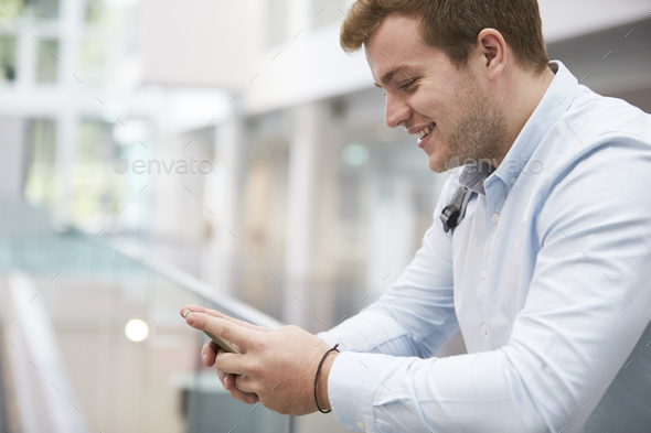 Adult male student using smartphone in university, close up - Stock Photo - Images
