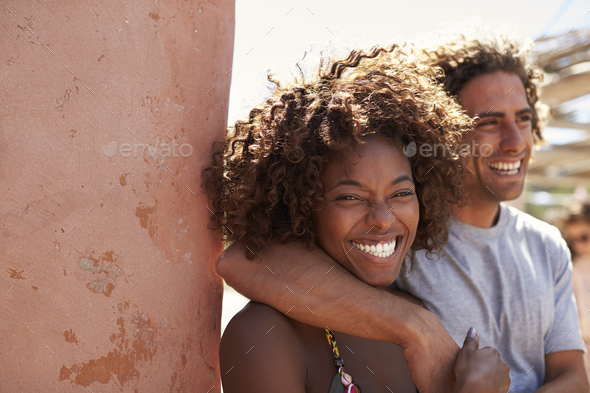 Mixed race couple eating at table by the sea, Ibiza, Spain - Stock Photo - Images