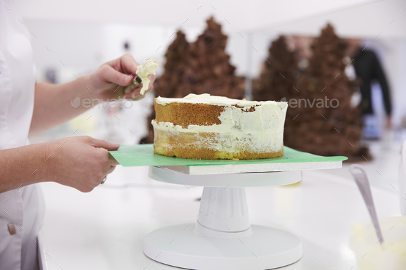 Close Up Of Woman In Bakery Decorating Cake With Icing - Stock Photo - Images