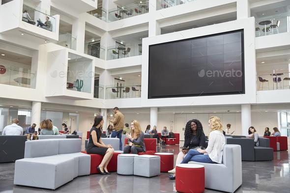 Students sit talking under AV screen in atrium at university - Stock Photo - Images