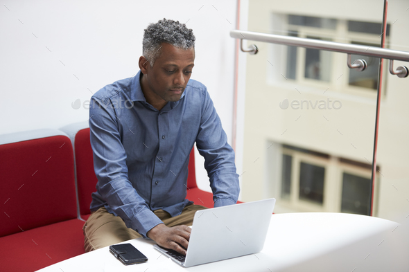 Middle aged black man uses laptop on mezzanine, elevated view - Stock Photo - Images