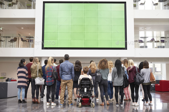 Students looking up at a big screen in university atrium - Stock Photo - Images