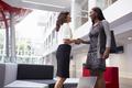 Two Businesswomen Shaking Hands In Lobby Of Modern Office