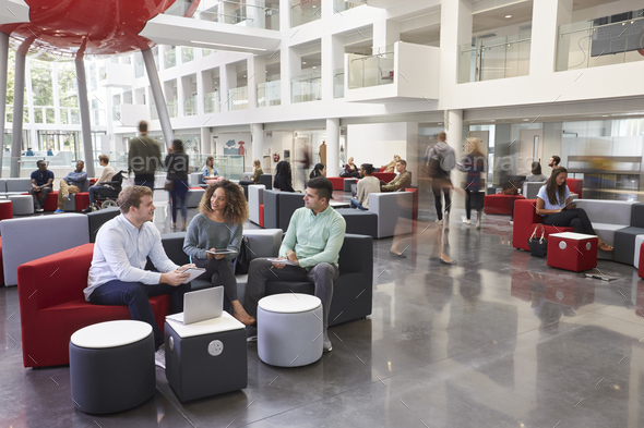 Students talking in busy university campus building - Stock Photo - Images