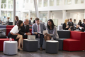 Businesspeople Meeting In Busy Lobby Of Modern Office