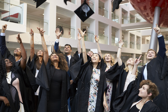 University students throwing their caps in the air on graduation day - Stock Photo - Images