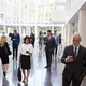 Download Businesspeople Using Technology In Busy Lobby Area Of Office from PhotoDune