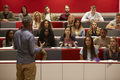 Back view of man presenting to students at a lecture theatre - PhotoDune Item for Sale