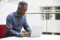Middle aged black man using laptop in a modern interior - PhotoDune Item for Sale