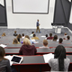 Man lectures students in lecture theatre, back row seat POV - PhotoDune Item for Sale