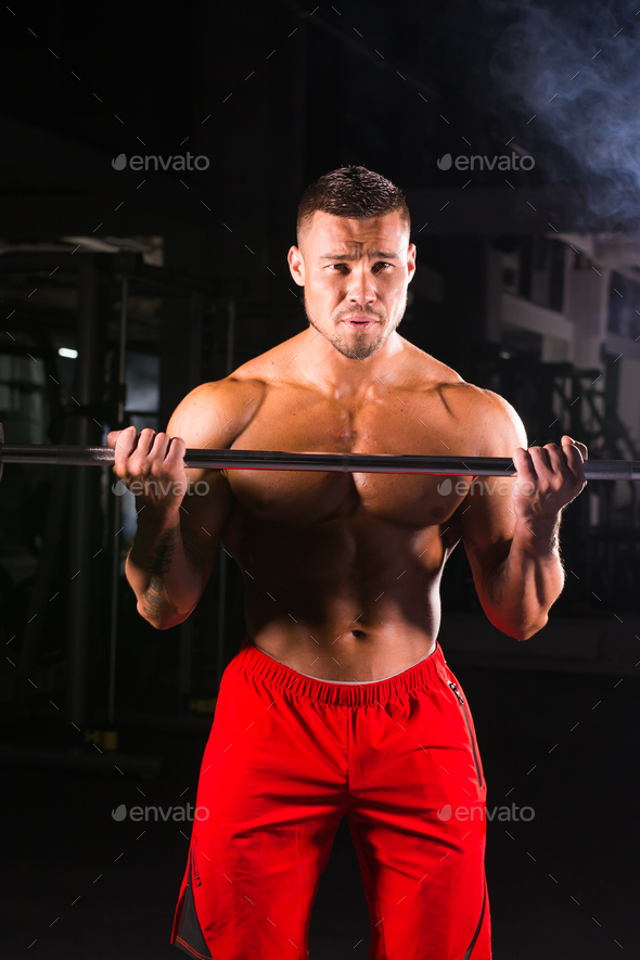 Athlete muscular bodybuilder in the gym training with bar - Stock Photo - Images