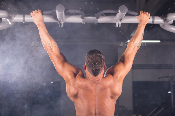 Athlete muscular fitness male model pulling up on horizontal bar in a gym. - Stock Photo - Images