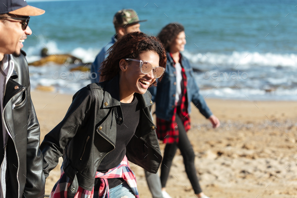 Cheerful african friends walking outdoors at beach. - Stock Photo - Images