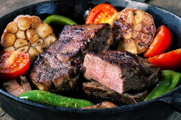 Appetizing beef steak in frying pan with vegetable garnish - Stock Photo - Images
