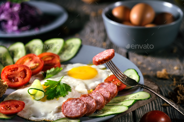 Fried eggs with vegetables and sausage on a wooden table - Stock Photo - Images