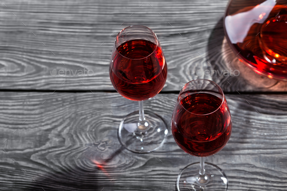 Decanter and two glasses of red wine on a wooden table - Stock Photo - Images