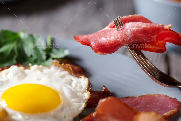 Fragment of appetizing bacon on a fork and fried eggs - Stock Photo - Images