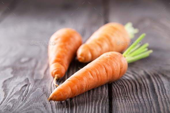 Three bright juicy carrots with green cuttings - Stock Photo - Images