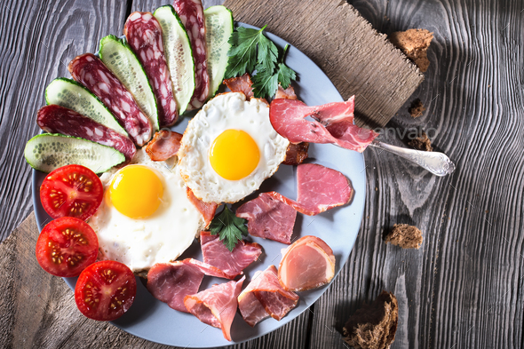 Fried eggs with bacon and vegetables on a wooden table - Stock Photo - Images
