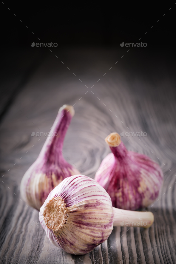 Three heads of garlic on a wooden table - Stock Photo - Images