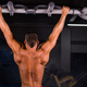 Rear view of muscular man doing pull ups at the gym - PhotoDune Item for Sale