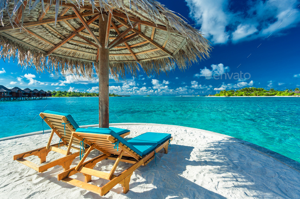 Two beach chairs under umbrella with ocean view in Maldives - Stock Photo - Images