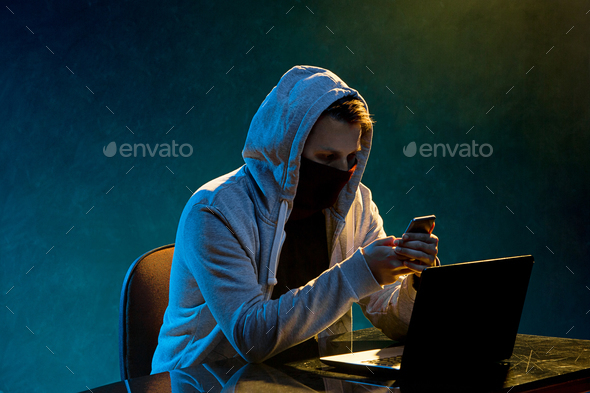 Hooded computer hacker stealing information with laptop - Stock Photo - Images