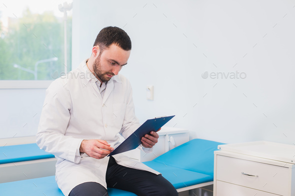 Portrait of handsome young doctor in office - Stock Photo - Images
