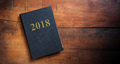 Vintage 2018 diary on wooden background - copy space