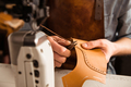 Man artisan sewing leather shoes indoors