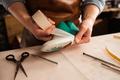 Close up of a cobbler modeling mens shoe