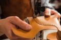 Close up of a cobbler stitching a part of shoe