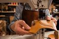 Man cobbler stitching leather patrs