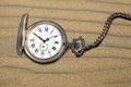 Antique pocket watch on sand