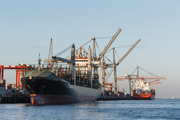 Cargo ships in port being loaded - Stock Photo - Images
