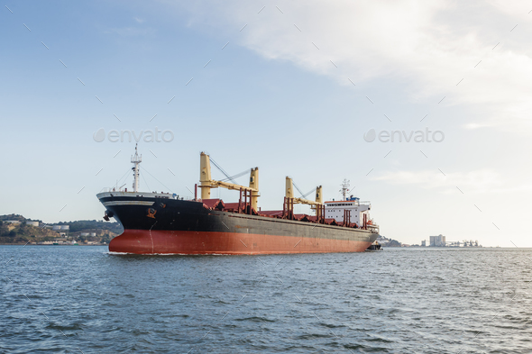 Cargo ships in river being tugged - Stock Photo - Images