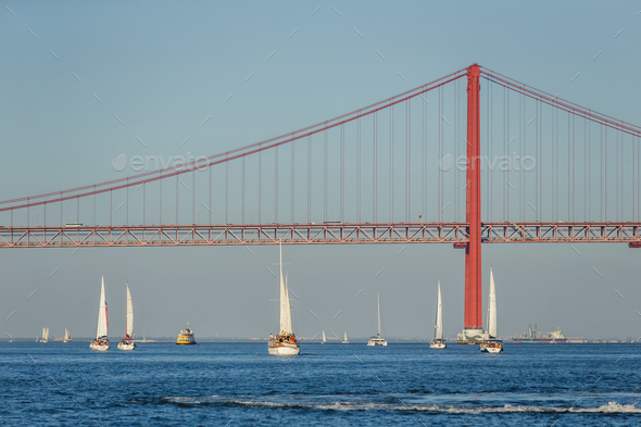 Boats sailing in river Tagus with bridge in Lisbon, Portugal - Stock Photo - Images