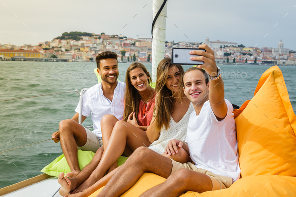 Group of friends having fun in boat in river - Stock Photo - Images