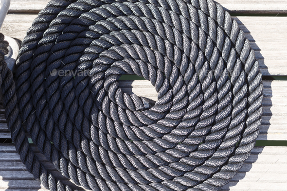 Close-up of a mooring rope on a wooden pier/ Nautical mooring ro - Stock Photo - Images