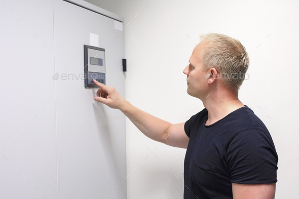 Male Computer Engineer Adjusting Air Conditioner In Datacenter - Stock Photo - Images