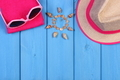 Seashells in shape of sun, sunglasses, straw hat and towel on boards, accessories for vacation