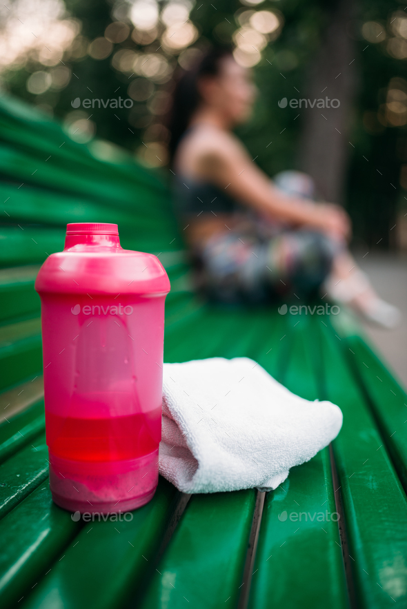 Sport bottle and towel on a bench in summer park - Stock Photo - Images