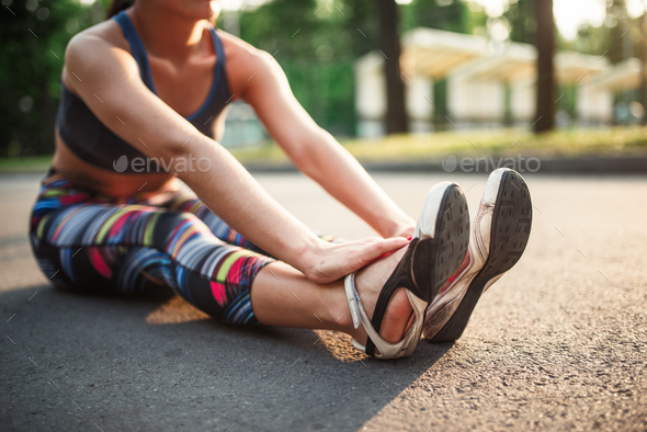 Athletic girl sitting on sidewalk in summer park - Stock Photo - Images