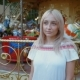 Young Attractive Blonde Girl Standing Near Carousel in Amusement Park. Beautiful Portrait of Woman