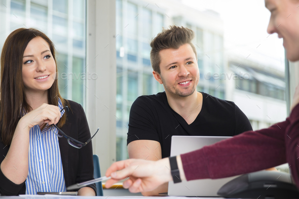Smiling Business People Looking At Colleague Explaining At Desk - Stock Photo - Images