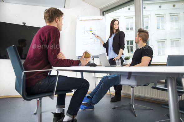 Businesswoman Explaining Graph To Coworkers In Office - Stock Photo - Images