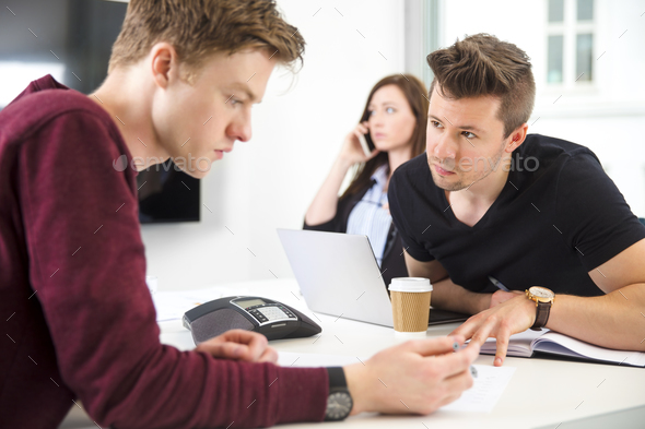 Businessmen Communicating While Colleague Using Smart Phone - Stock Photo - Images